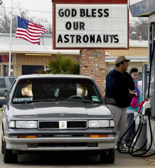 "Gerardo Hernandez (R front) prepares to pump gas at a station where a marquee reads ""God Bless Our Astronauts"" beneath an American flag flying at half mast in tribute to the seven astronauts who died aboard the space shuttle Columbia, in Kilgore, Texas 07 February 2003. (Mike Nelson/Getty Images)"