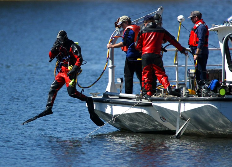 Dive team member enter the Toledo Bend reservoir near the dam on the Louisiana side in the search for debris from the Space shuttle Columbia 11 February 2003 in Anacoco. Several dive teams searched the lake as hundreds of searchers canvassed the heavy forest in Texas. (Paul Buck/Getty Images)