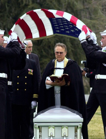 The flag is lifted from the casket of space shuttle Columbia Mission Specialist Captain David Brown in Arlington National Cemetery March 12, 2003 in Arlington, Virginia. Brown, one of the seven member crew on the last voyage of space shuttle Columbia, was buried with full naval honors. (Stefan Zaklin/Getty Images)