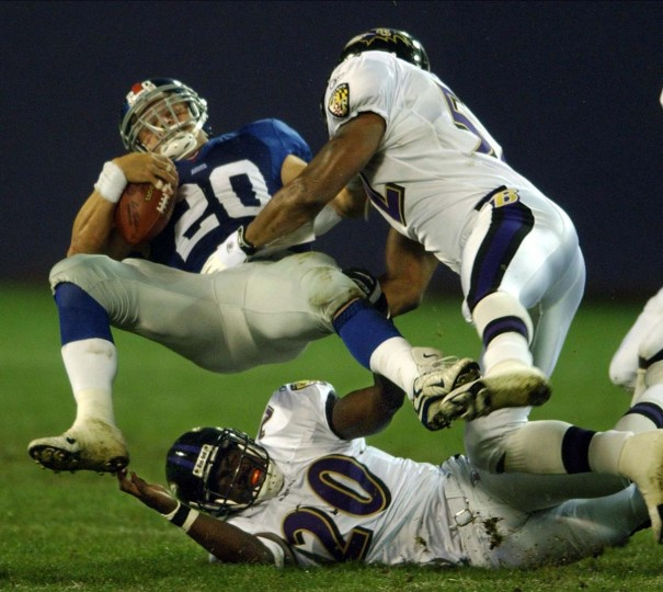 Ray Lewis lays a crushing hit on Giants running back Sean Bennett, who falls backward over Ed Reed during a preseason game on Aug. 29, 2002. (Karl Merton Ferron/Baltimore Sun Photo)