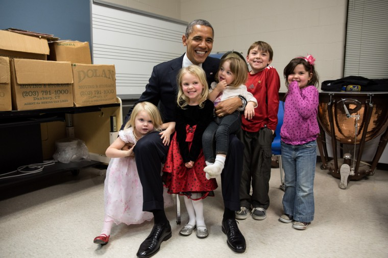 """Dec. 16, 2012: """"Two days after the shootings at Newtown, the President traveled to Connecticut to meet with the victims' families and give remarks at a prayer vigil. The President spent hours greeting family members. Difficult as that was for everyone, the one moment that helped sooth the pain was when he posed for a photo with the siblings and cousins of Emilie Parker, one of the 20 children who died that day in Newtown. I see both sadness and hope in this photograph, and I know after a lot of tears that day, it meant so much to the President that everyone was able to smile for a moment in this family photo. Thanks to the Parker family for allowing us to show this photograph publicly."""" (Official White House Photo by Pete Souza)"""