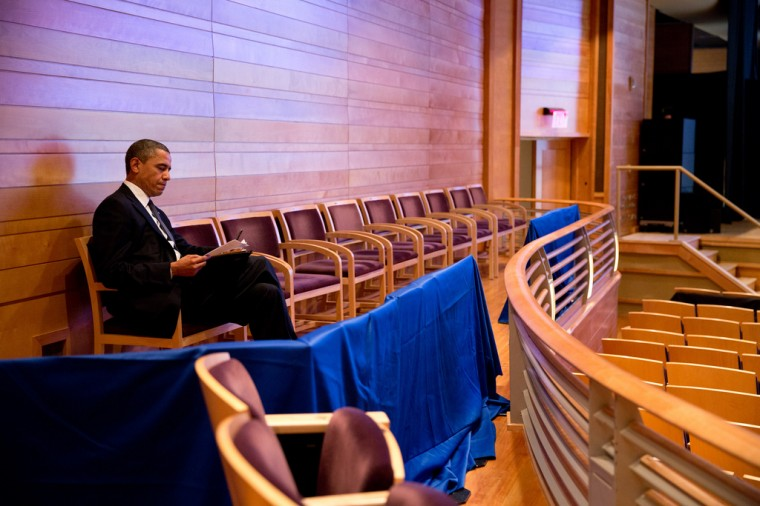 """Dec. 16, 2012: """"The President works on his Newtown speech at an auditorium in suburban Washington. Two days earlier, I had photographed him when John Brennan first briefed him on the shootings. Throughout that day, he reacted as we all did, which people witnessed when he delivered his statement a few hours later. Before we headed to Newtown for the Sunday night vigil, he went to watch his daughter Sasha, 11, at her rehearsal for the Nutcracker; he would be unable to attend her performance because of the trip to Newtown. During breaks in the rehearsal, he worked on his speech. His expression in this photograph may be subtle to the viewer, but not to me. There is emotion and resolve etched on his face, and he knew the importance of this speech for the nation."""" (Official White House Photo by Pete Souza)"""