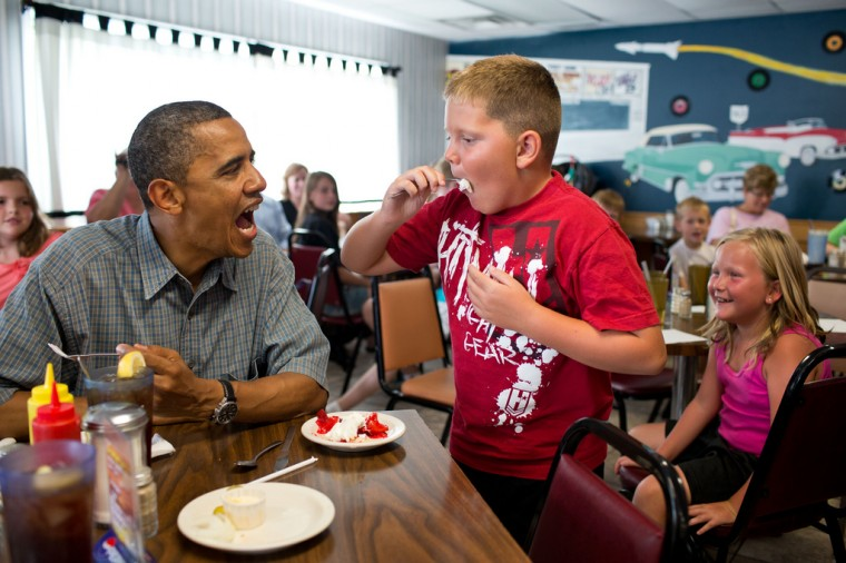 """July 5, 2012: """"'Anyone want to try a piece of my strawberry pie,' the President asked those at adjacent tables during a stop for lunch at Kozy Corners restaurant in Oak Harbor, Ohio. A young boy said yes and came over for a big bite of pie."""" (Official White House Photo by Pete Souza)"""