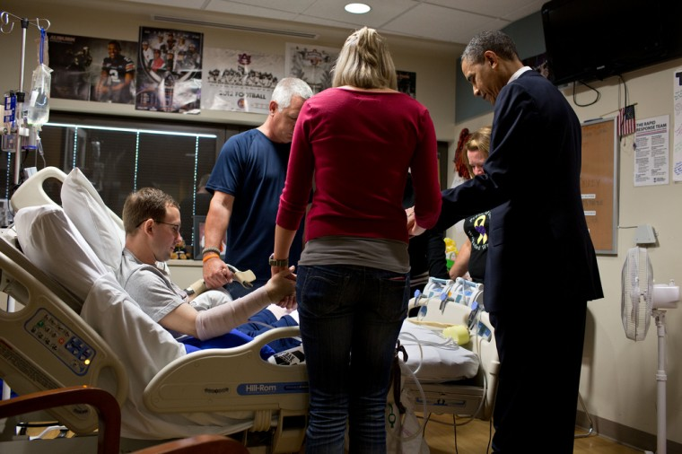 """June 28, 2012: """"The President prays with a wounded service member and his family during a visit to Walter Reed National Military Medical Center in Bethesda, Md. The President likes to make a few trips a year to Walter Reed to visit wounded warriors and their families."""" (Official White House Photo by Pete Souza)"""