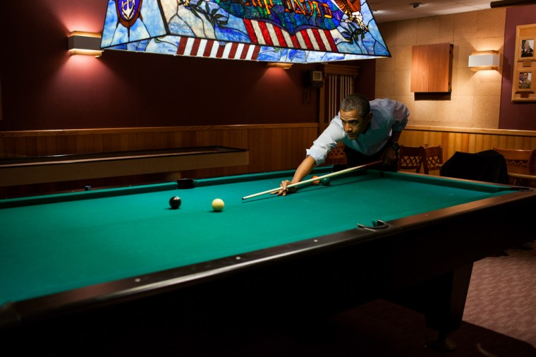 """May 19, 2012: """"Following the conclusion of the G8 Summit, the President plays a game of pool in the Holly Cabin at Camp David."""" (Official White House Photo by Pete Souza)"""