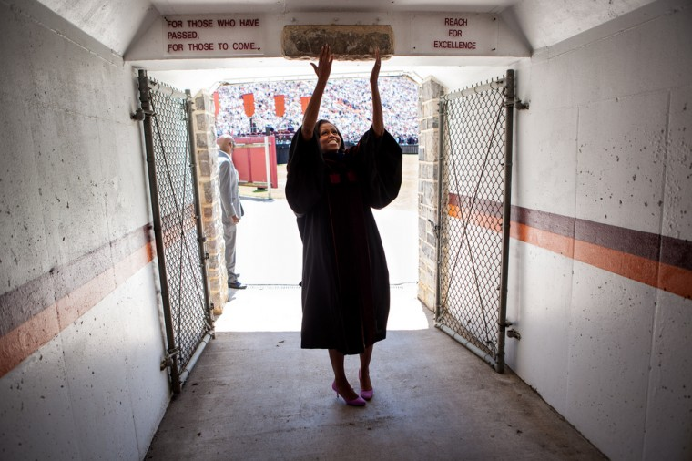 """May 11, 2012: """"Lawrence Jackson made this great photograph of the First Lady touching the Hokie Stone before walking onto the field at Lane Stadium to give the Virginia Tech commencement address in Blacksburg, Va."""" (Official White House Photo by Lawrence Jackson)"""