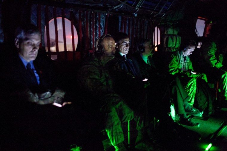 """May 1, 2012: """"In Afghanistan, there was virtually no light inside the helicopter as we flew from Kabul back to Bagram Air Field after the President had met with Afghan President Hamid Karzai. (For the photo buffs, this photograph was taken at ISO 6400, 1/5 second at f/1.4.) Flanking the President are General John Allen, Commanding General of U.S. Forces in Afghanistan, and U.S. Ambassador to Afghanistan Ryan Crocker. Denis McDonough, Deputy National Security Advisor, is at left."""" (Official White House Photo by Pete Souza)"""