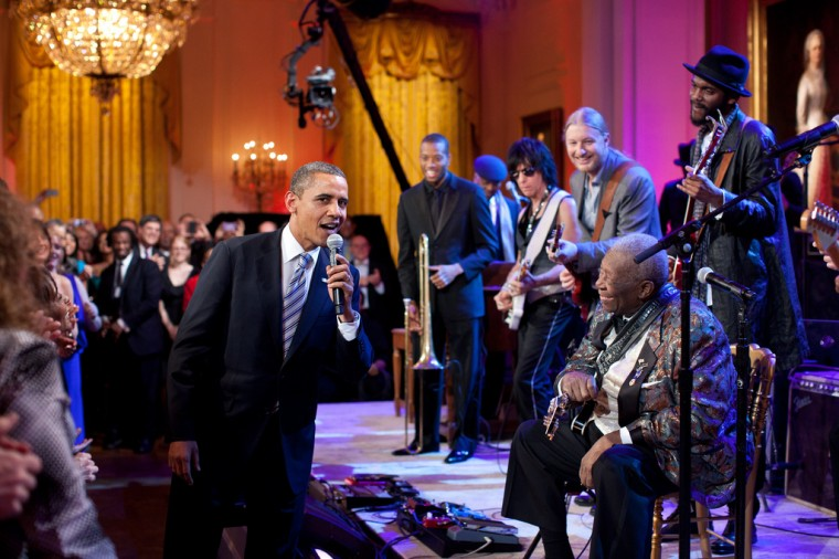 """Feb. 21, 2012: """"Egged on by B.B. King, at right, the President joins in singing 'Sweet Home Chicago' during the 'In Performance at the White House: Red, White and Blues' concert in the East Room. Participants include, from left: Troy 'Trombone Shorty' Andrews, Jeff Beck, Derek Trucks, B.B. King, and Gary Clark, Jr."""" (Official White House Photo by Pete Souza)"""