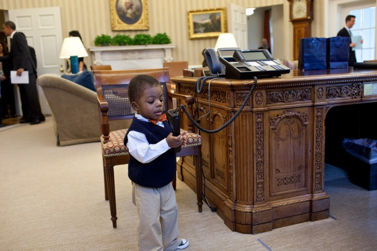 """Feb. 7, 2012: """"Kids will be kids. After the President had welcomed Lauren Fleming, the March of Dimes national ambassador, and her family in the Oval Office, her brother, Corbin Fleming, started to play with the President's telephone. Fortunately, he wasn't able to get through to a head of state."""" (Official White House Photo by Pete Souza)"""