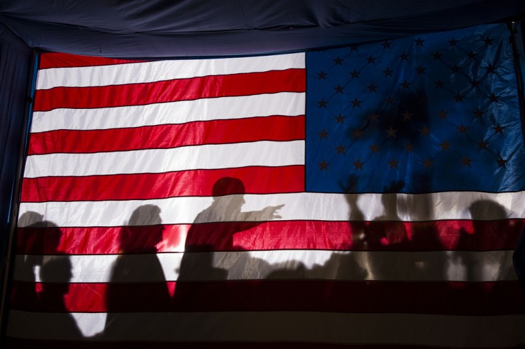 """Nov. 3, 2012: """"I had noticed the possibility of a potential good photograph if the President were to pass by this flag as he departed an evening campaign rally in Dubuque, Iowa. So I planted myself backstage as he finished working a ropeline and managed to get one usable frame as he walked by."""" (Official White House Photo by Pete Souza)"""