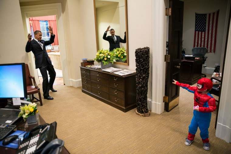 """Oct. 26, 2012: """"The President pretends to be caught in Spider-Man's web as he greets Nicholas Tamarin, 3, just outside the Oval Office. Spider-Man had been trick-or-treating for an early Halloween with his father, White House aide Nate Tamarin in the Eisenhower Executive Office Building. I can never commit to calling any picture my favorite, but the President told me that this was HIS favorite picture of the year when he saw it hanging in the West Wing a couple of weeks later."""" (Official White House Photo by Pete Souza)"""