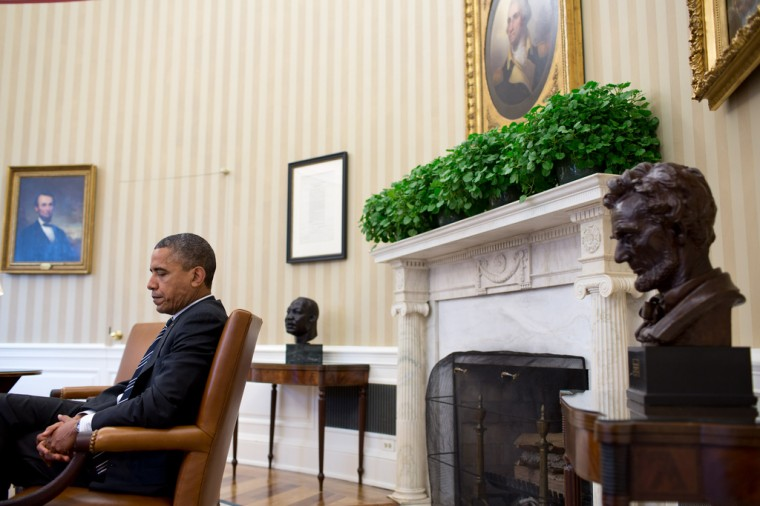 """Sept. 28, 2012: """"A candid portrait of the President during a meeting, juxtaposed with the paintings of Abraham Lincoln and George Washington, busts of Martin Luther King, Jr., and Abraham Lincoln, and the Emancipation Proclamation. It's a difficult angle to get because I had to sit in front of the closed Oval Office door and hope that no one would open the door and knock me over."""" (Official White House Photo by Pete Souza)"""