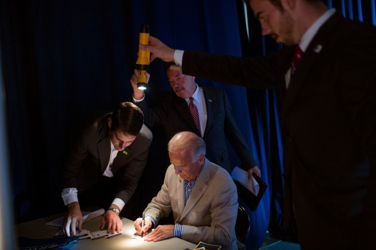 """Sept. 2, 2012: """"David Lienemann made this unusual photo as staff held flashlights so the Vice President could see as he signed autographs backstage at West York Area High School in York, Pa."""" (Official White House Photo by David Lienemann)"""