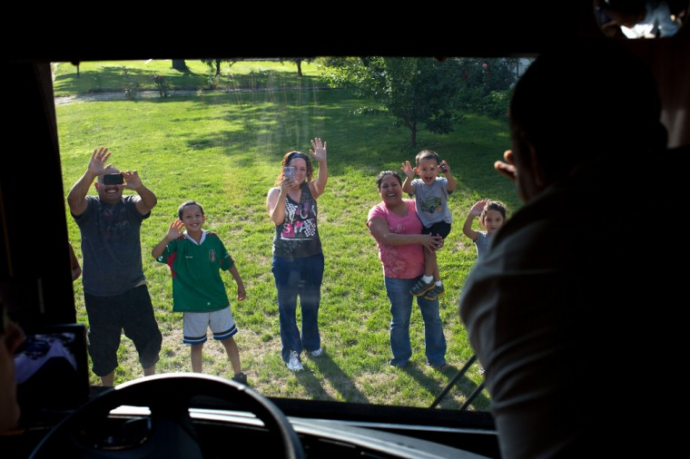 """Aug. 14, 2012: """"The President waves from his campaign bus to people lining the motorcade route in Iowa."""" (Official White House Photo by Pete Souza)"""