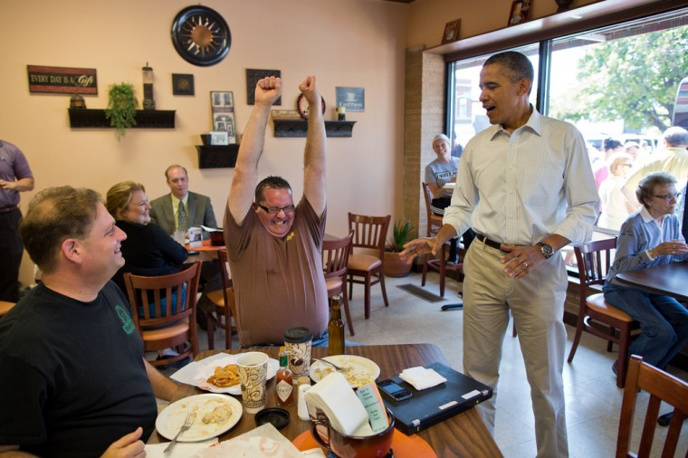 """Aug. 14, 2012: """"How about a White House beer? The President was greeting patrons at Coffee Connection in Knoxville, Iowa, when this customer asked him about the White House beer. The President said he thought he might have some on his campaign bus and asked an aide to check. A few minutes later, the President delivered a bottle and the customer reacted in celebration."""" (Official White House Photo by Pete Souza)"""