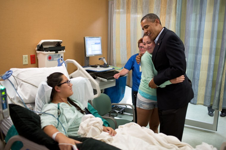 """July 22, 2012: """"The President hugs Stephanie Davies, who helped her friend, Allie Young, left, stay alive after she was shot during the movie theater shootings in Aurora, Colo. The President visited patients and family members affected by the shootings at the University of Colorado Hospital. The President later told their story in a news conference."""" (Official White House Photo by Pete Souza)"""