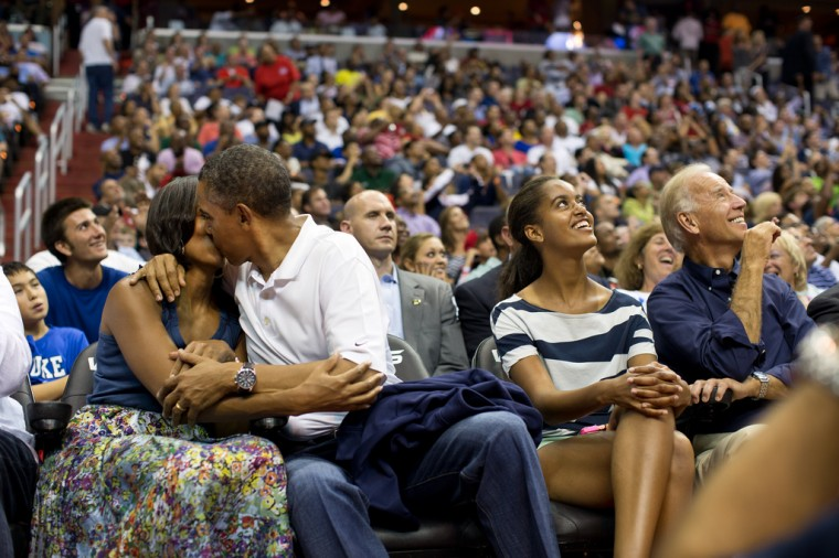 """July 16, 2012: """"The President and First Lady were attending the game between the U.S. Men's Olympic basketball team and Brazil in Washington, D.C. During the first half, the jumbotron flashed couples on their 'Kiss Cam', where they are then induced by the crowd to kiss each other. But neither the President or First Lady saw themselves when they were flashed on the 'Kiss Cam', and some in the audience booed when they didn't kiss. At halftime, as we walked to the locker room to visit the U.S. team, daughters Malia and Sasha were asking their parents why they hadn't kissed during their 'Kiss Cam' moment. Both the President and First Lady said they hadn't even realized what had happened and didn't know why people were booing. So in the second half, when they appeared again on the 'Kiss Cam', the President leaned over to kiss the First Lady amidst audience cheers as Malia and the Vice President watched overhead on the jumbotron."""" (Official White House Photo by Pete Souza)"""