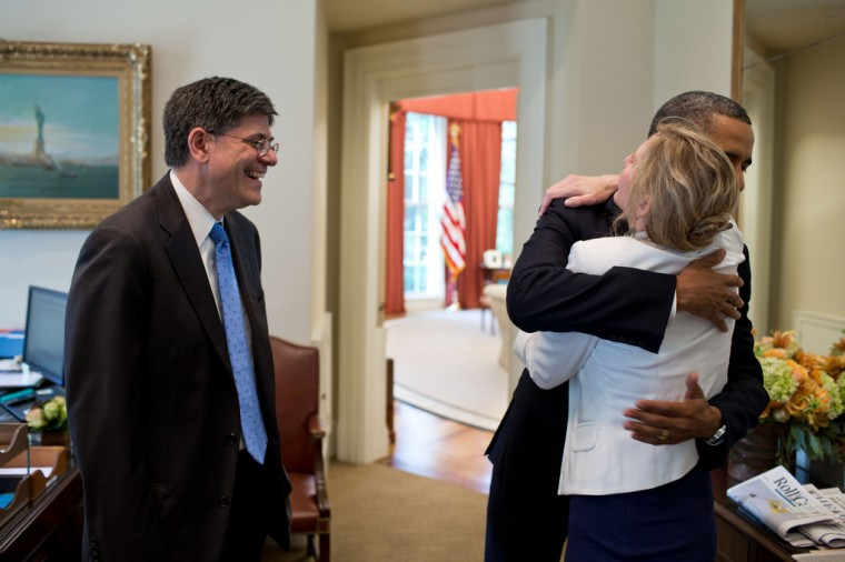 """June 28, 2012: """"This was the day that the U.S. Supreme Court ruled on the Affordable Health Care Act. Before the President came downstairs from the residence that morning, the split-screen television in the Outer Oval Office was flashing bulletins that the Court had overturned the act. Kathy Ruemmler, the White House counsel, came rushing in and told me and the President's secretary just the opposite. Kathy then departed and a few minutes later the President arrived at the Oval and saw the same inaccurate information on the television. Kathy soon reappeared to tell the President that the Court had indeed upheld the Act, and that the TV reports had it wrong. He then gave her a big hug, as Chief of Staff Jack Lew watched at left."""" (Official White House Photo by Pete Souza)"""