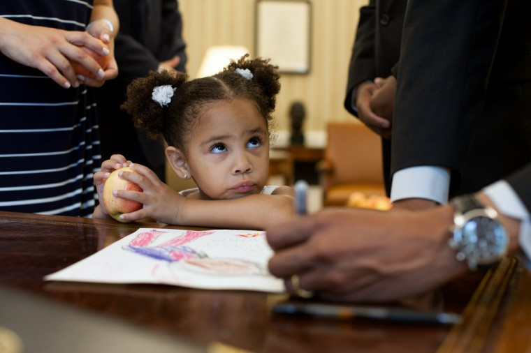 """May 25, 2012: """"Luz Graham-Urquilla, 4, watches as the President signs her drawing at the Resolute Desk in the Oval Office."""" (Official White House Photo by Pete Souza)"""