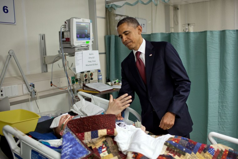 "May 1, 2012: ""For the President, this was one of the most poignant moments of the his first term. He was visiting wounded warriors in the intensive care unit at Bagram Air Field in Afghanistan. He had just presented a Purple Heart to Sgt. Chase Haag, who had been injured by an IED just hours before. Sgt. Haag was covered with a blanket and it was difficult to see how badly he was injured. He was also seemingly unconscious, or perhaps just asleep. The President whispered in his ear so not to wake him. Just then, there was a rustling under the blanket and Sgt. Haag, eyes still closed, reached his hand out to shake hands with the President. 'I'll never forget that moment,' someone else in the room later told me."" (Official White House Photo by Pete Souza)"