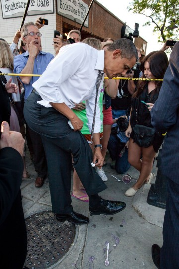 """April 24, 2012: """"The President wipes off his trousers after being splattered by frozen yogurt while shaking hands along a ropeline in Boulder, Colo. University of Colorado student Kolbi Zerbest had placed her cup of yogurt on the ground while trying to shake hands with the President, and someone else inadvertently kicked the cup."""" (Official White House Photo by Pete Souza)"""