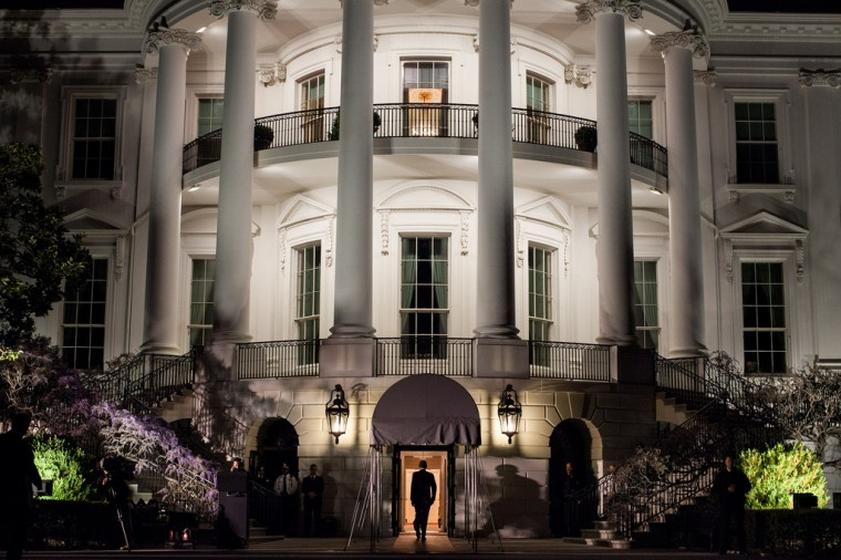 """March 30, 2012: """"We had just arrived aboard the Marine One helicopter on the South Lawn and the President was walking into the White House. I had seen this scene several times but had never been able to quite capture it the way I wanted. Here, finally, arriving at night, I was able to frame him walking into the light of the Diplomatic Reception Room, with the added bonus of his shadow being cast from the television lights off to the left."""" (Official White House Photo by Pete Souza)"""