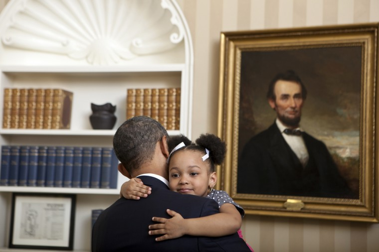 """Feb. 1, 2012: """"Lawrence Jackson captured this cute photograph of the President holding Arianna Holmes, 3, before taking a departure photo with members of her family in the Oval Office."""" (Official White House Photo by Lawrence Jackson)"""