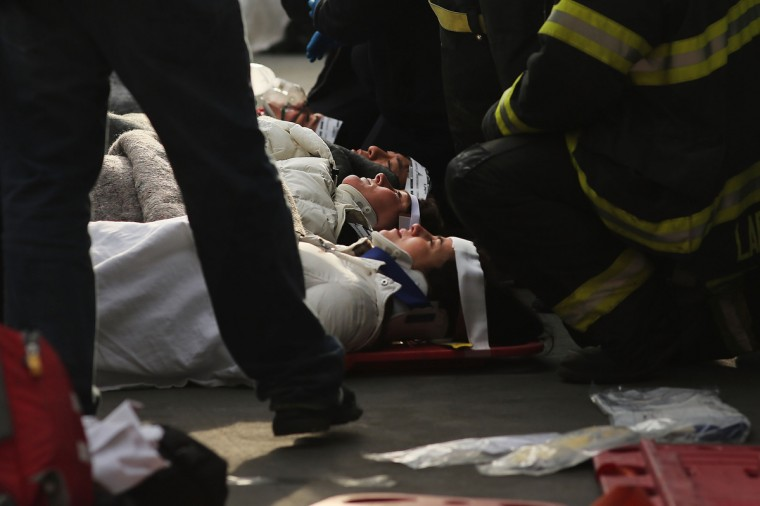 Injured passengers are aided following an early morning ferry accident during rush hour in Lower Manhattan in New York City. About 50 people were injured in the accident, which left a large gash on the front side of the Seastreak ferry at Pier 11. (Spencer Platt/Getty Images)