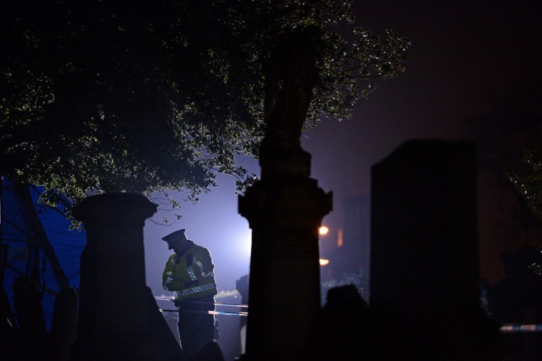 A police officer stands on duty at Monkland Cemetery as forensic officers continue to exame a burial plot in Coatbridge, Scotland. Forensic specialists are exhuming remains at a gravesite in search of 11 year old school girl Moira Anderson, who went missing in 1957. (Jeff J Mitchell/Getty Images)