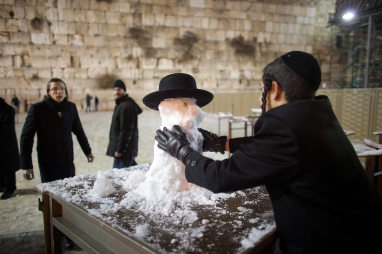 An ultra-Orthodox Jewish boy builds a snow man at the Western Wall in Jerusalem, Israel. Snow and strong winds have affected regions across the Middle East. (Uriel Sinai/Getty Images)