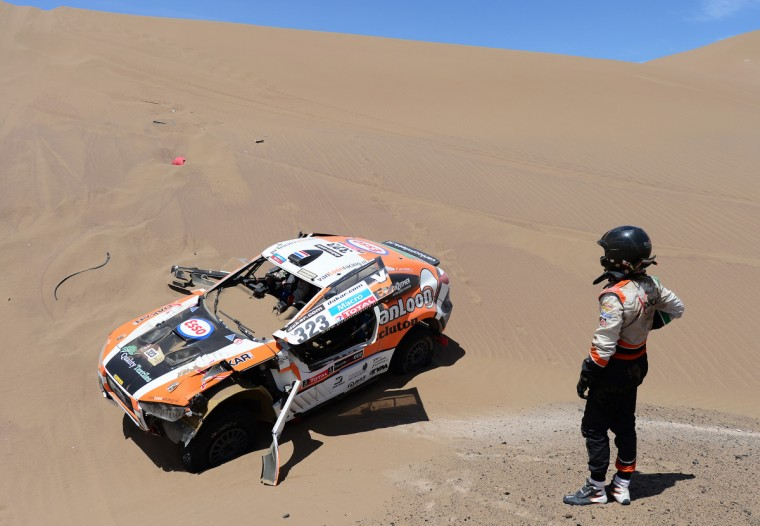 Marc Wams of team HRX waits for driver Erik Van Loon to get out of the car after crashing during in stage 6 from Arica to Calama during the 2013 Dakar Rally on January 10, 2013 in Arica, Chile. (Shaun Botterill/Getty Images)