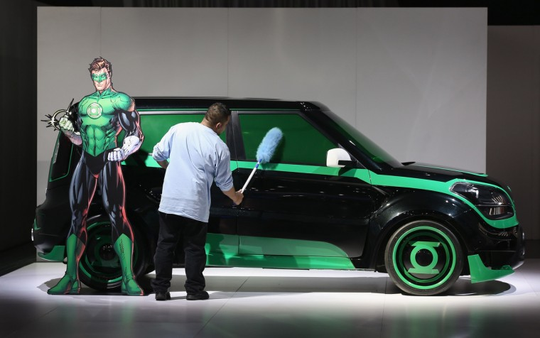 Angel Palizio dusts a Kia Soul with the DC Comics package during the media preview at the North American International Auto Show. (Scott Olson/Getty Images)