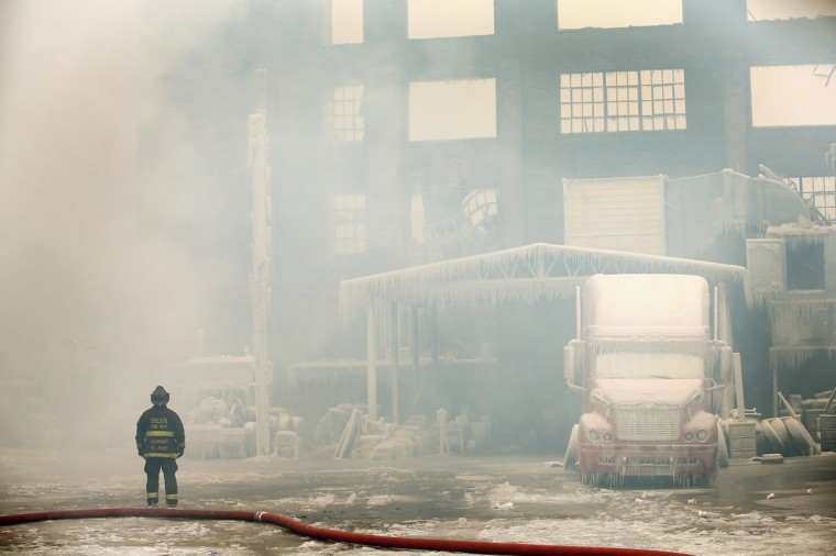 Firefighters work to extinguish a massive blaze at a vacant warehouse in Chicago, Illinois. More than 200 firefighters battled a five-alarm fire as temperatures were in the single digits. (Scott Olson/Getty Images)
