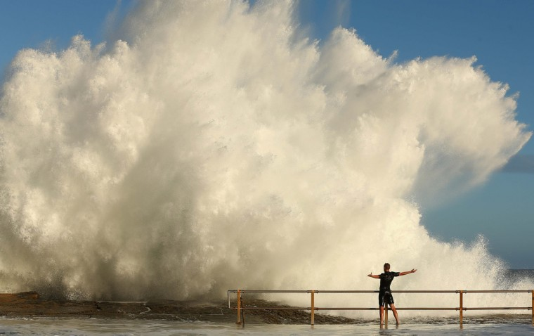A man hangs onto the railing of North Curl Curl ocean pool after winds and rain battered Sydney last night producing large swell in Sydney, Australia. Parts of Sydney are experienced record rainfall after ex-cyclone Oswald swept through the city last night. (Cameron Spencer/Getty Images)