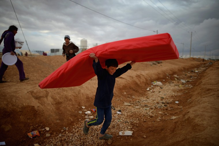 A boy carries a mattress as Syrian refugees go about their daily business in theZa'atari refugee camp on January 29, 2013 in Mafrq, Jordan. Record numbers of refugees are fleeing the violence and bombings in Syria to cross the borders to safety in northern Jordan and overwhelming the Za'atari camp. The Jordanian government are appealing for help with the influx of refugees as they struggle to cope with the sheer numbers arriving in the country. (Jeff J Mitchell/Getty Images)