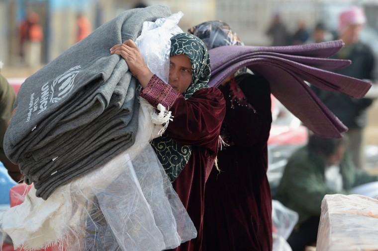 Refugees from Syria collect blankets and supplies from the UNHCR as they arrive at the Za'atari refugee camp on January 30, 2013 in Mafrq, Jordan. (Jeff J Mitchell/Getty Images)