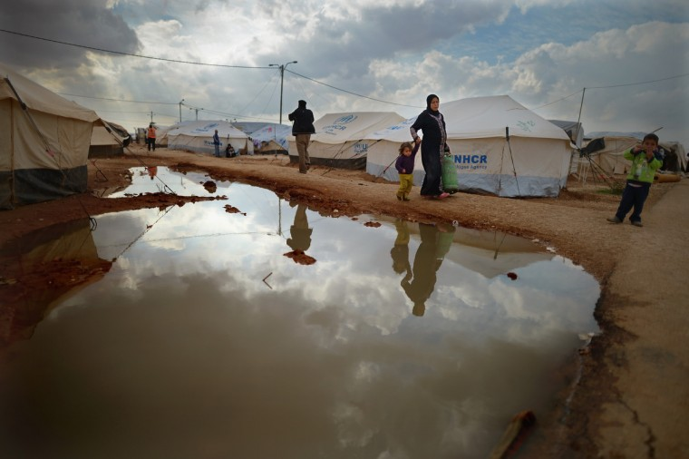 A woman carries a gas canister as Syrian refugees go about their daily business in the Za'atari refugee camp on January 30, 2013. (Jeff J Mitchell/Getty Images)