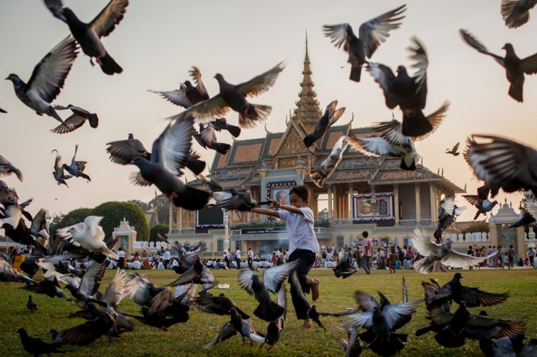 A young boy runs through a group of Pigeons in front of the Royal Palace in Phnom Penh, Cambodia. Former King Norodom Sihanouk died of a heart attack last October in Beijing at the age of 89. For the past three months his body has been lying in state at the Royal Palace. Officials expect more than one million people to line the streets tomorrow to witness the funeral procession. The former kings body will be transported to a cremation site where it will be kept for three days before his wife and son are expected to light the pyre. (Chris McGrath/Getty Images)