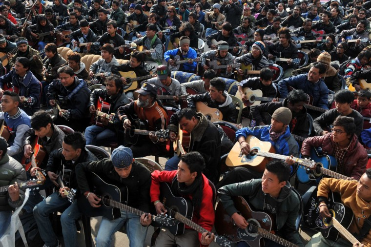 """Musicians play John Lennon's """"Imagine"""" in a memorial tribute to the 23-year old Indian gang rape victim, during a mass guitar ensemble played by some 600 guitarists in Darjeeling. (Diptendu Dutta/Getty Images)"""
