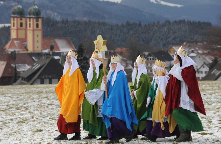 """Young carol singers make their way over a snowy meadow as in background can be seen the """"Maria Himmelfahrt"""" (Ascension of Mary) conventual church in St. Maergen, southern Germany. The 2013 """"Three King's Action"""" charity focuses on the plight of children in Tansania. (Patrick Seeger/Getty Images)"""