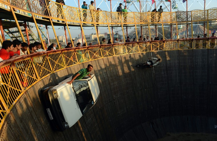 Indian daredevils perform car and bike stunts during an annual fair in Mumbai. The ten day-long fair is being held in honor of the Sufi saint Makhdoom Ali Mahimi on the dusty Mahim beach, which is full of people on giant wheels, toy trains and enjoying gravity-defying stunts in the 'Valley of Death.' (Punit Paranjpe/Getty Images)