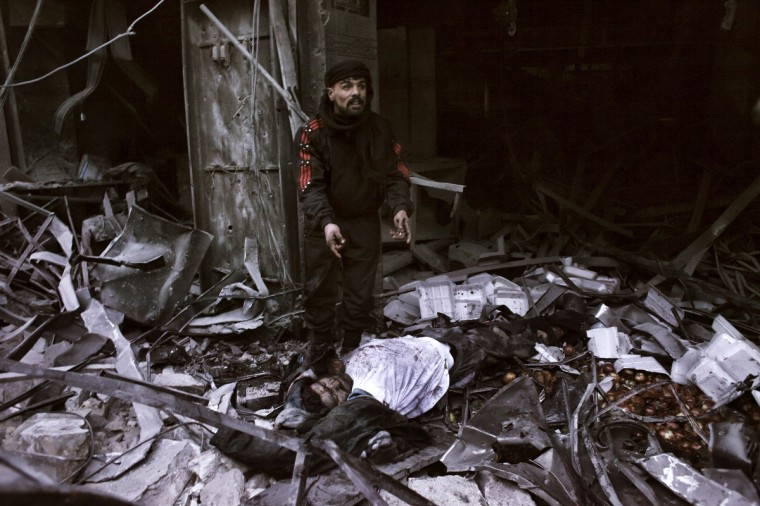 """A rebel fighter stands next to the body of a man killed after a missile targeted a building in the al-Mashhad neighborhood of Aleppo on January 7, 2013. The United Nations recently denounced a """"proliferation of serious crimes including war crimes"""" in Syria, as ever more horrifying images and videos emerge from the country. (Getty Images)"""