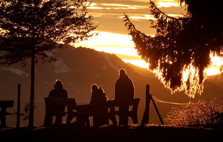 Tourists enjoy the view from the Auerberg mountain near Bernbeuren, southern Germany, as sun sets behind an Alps panorama. (Karl-Josef Hildenbrand/Getty Images)