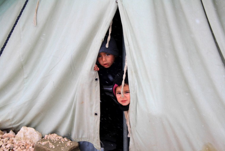 Syrian refugee children peer from a tent supplied by the United Nations High Commissioner for Refugees (UNHCR) in al-Marj, in the eastern Lebanese Bekaa Valley as stormy weather sparked widespread flooding, prompting chaos on the roads and a nationwide school closure. The number of Syrian refugees in Lebanon is already totaling 156,000, according to UN figures, and 200,000 according to the Lebanese government estimates. (Hassan Jarah/Getty Images)