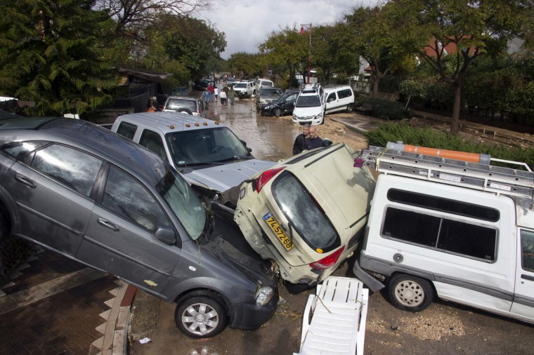 Israeli men look at the damaged cars in Beit Hefer near the Meditrranean coastal city of Netanya, north of Tel Aviv after heavy rains overnight. Israel and the Palestinian territories have been lashed by heavy rain and high winds since January 6, which has caused flooding across the region. (Jack Guez/Getty Images)