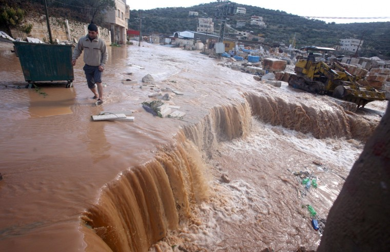 A man walks through rain water in the village of Qabatiya, in the Israeli occupied West Bank near the northern city of Jenin as rain storms and snow engulfs the Levant. (Saif Dahlah/Getty Images)
