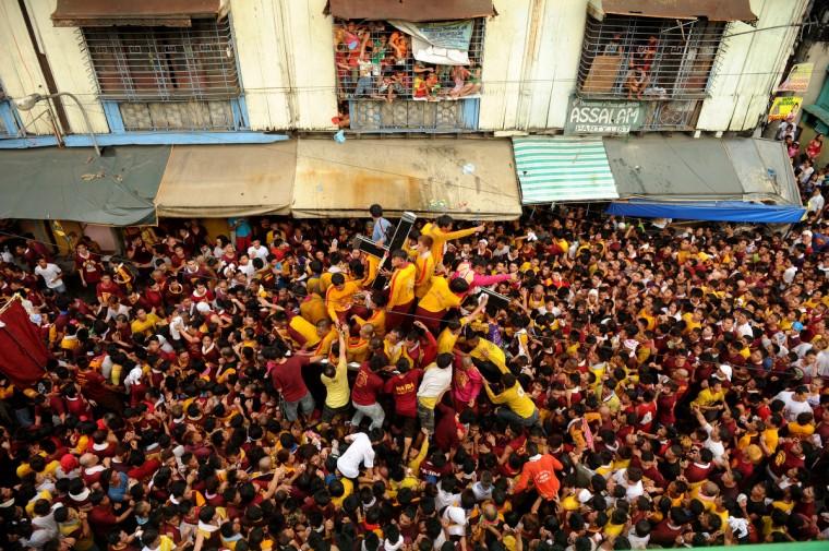 A sea of Catholic devotees jostle for position as they try to touch the life-size statue of the Black Nazarene during the annual procession in honor of the centuries-old icon of Jesus Christ in Manila. Masses of Catholic devotees swept through the Philippine capital on January 9, in a spectacular outpouring of passion for a centuries-old icon of Jesus Christ that many believe can perform miracles. (Noel Celis/Getty Images)