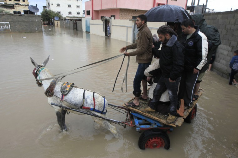A Palestinian man uses his donkey cart to transport people across a flooded street in the Rafah refugee camp, in the southern Gaza Strip. A storm has hit the eastern Mediterranean coast and heavy rains with flooding are forecast in Israel and the Palestinian territories for the next couple of days, with a good chance of snow falling in the higher elevations. (Said Khatib/Getty Images)