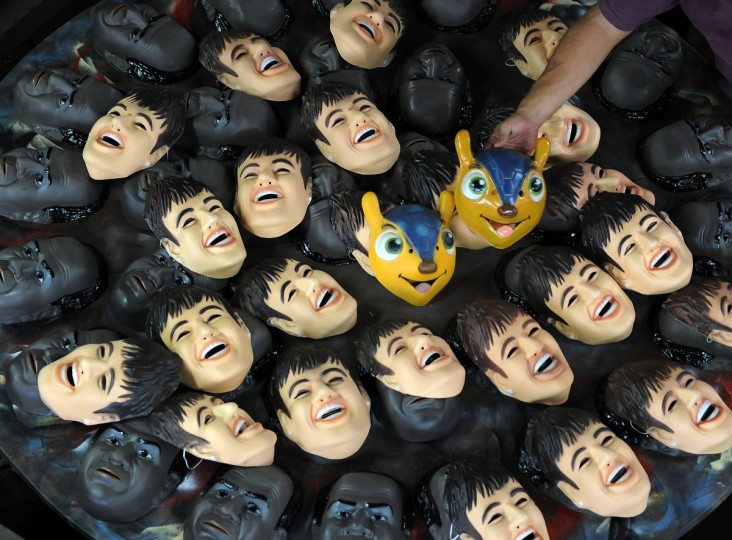 """A worker shows masks of Brazilian football star Neymar, the president of the Brazilian Supreme Court Joaquim Barbosa and the mascot of the Brazil 2014 FIFA World Cup, """"Tatu Bola-Fuleco"""", at the carnival masks factory Condal, in Sao Goncalo, about 35 km from downtown Rio de Janeiro. Rio's world famous carnival takes place February 9-12. (Venderlei Almeida/Getty Images)"""