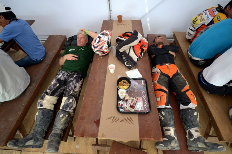 France's Patrice Carillon (R) and an unidentified biker sleep during the breakfast before the Stage 5 of the Dakar 2013 between Nazca and Arequipa, Peru, on January 9, 2013. (Franck Fife/Getty Images)